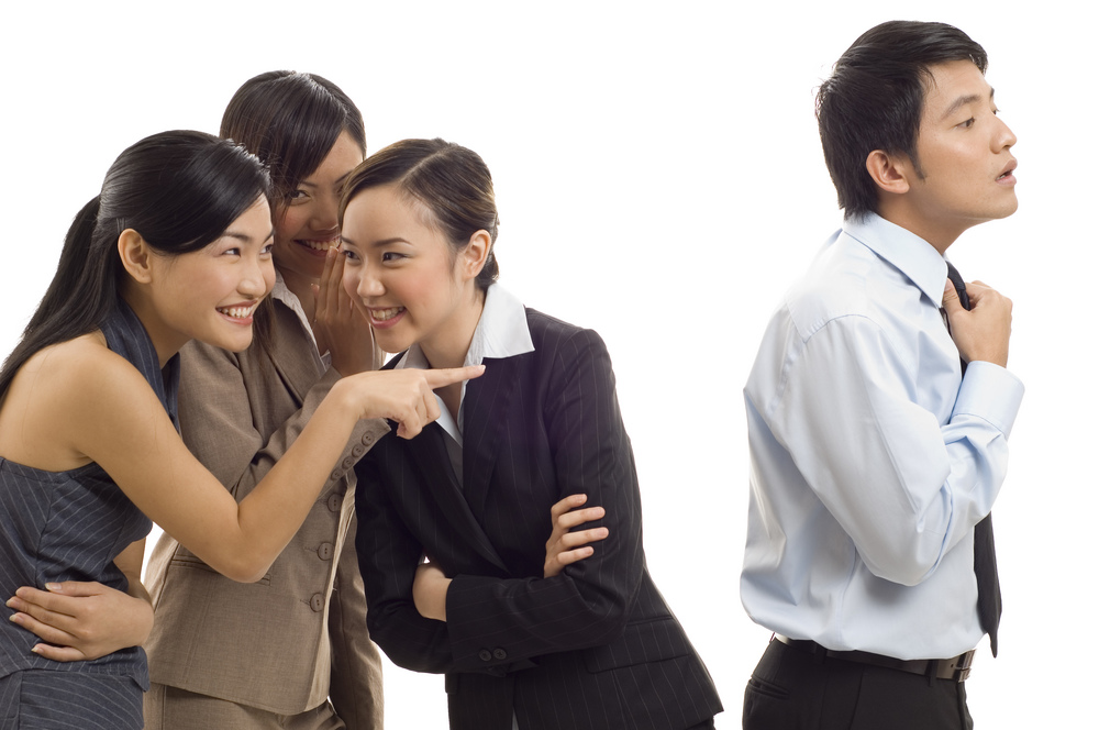 Three attractive young asian businesswomen gossip about one of their colleagues